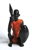 Wooden figure of an African Warrior front view. A carved figure of an African warrior with clothes made of dried leather, viewed from the front Royalty Free Stock Images