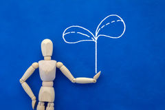 Wooden figure on  blue background with drawing of tree eco conce Royalty Free Stock Photo