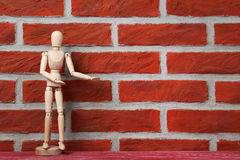 Wooden figure. On a brick wall background Stock Photography