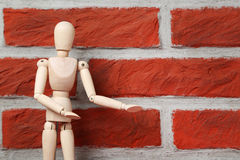 Wooden figure. On a brick wall background Stock Image