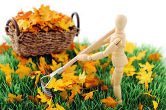 Wooden figure cleanup the garden from autumn leave Royalty Free Stock Photo