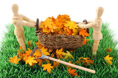 Wooden figure cleanup the garden from autumn leave Stock Photo