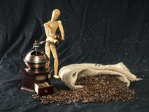 Wooden figure handling with a coffee grinder Stock Images