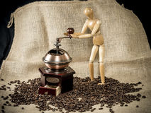 Wooden figure handling with a coffee grinder Stock Image