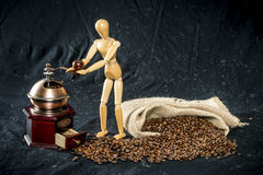 Wooden figure handling with a coffee grinder Stock Photography