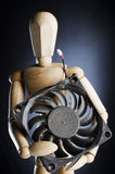 Wooden figure holding computer fan. stock images