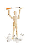 Wooden figure holding medicine injector Stock Image