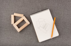 Wooden figure of house, drawing in notepad, pencil lay on grey f Royalty Free Stock Image