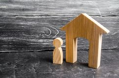 A wooden figure of a man stands near a wooden house on a gray concrete background. Concept of real estate, renting and buying. An apartment. Search for a life royalty free stock photos