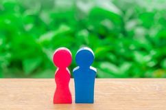 The wooden figure of a man and a woman on a green bokeh background. Concept of love, lovers, romance. Gender relations. Minimalism. Marriage and wedding stock image