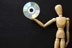 Wooden Figure Manikin Human Artist Draw Painting wood doll. Holding a compact disk royalty free stock image