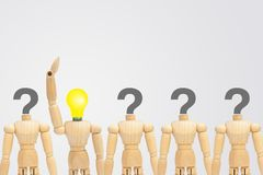 Wooden figure mannequin with light bulb head standing out row of other figures with question mark on head. royalty free stock image