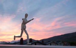 Wooden figure mannequin running. At sunset stock photos