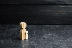 Wooden figure of mother and child. Concept of pregnancy, childbirth and upbringing. Fortunity. Education and guardianship of child. Ren. Independent child stock image