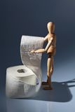 Wooden figure on a roll toilet paper Stock Photography