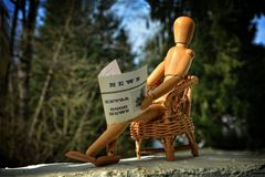 Wooden figure sitting on patio chair and reading newspaper Royalty Free Stock Images