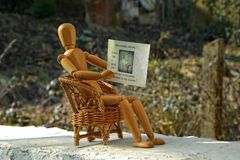Wooden figure sitting on patio chair and reading newspaper Royalty Free Stock Image