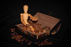 Wooden figure sitting in a wooden box with money Stock Photo