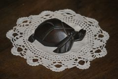Wooden figure of turtle. Brown wooden figure of turtle on the white napkin Stock Photo
