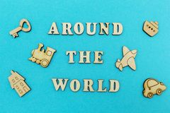 Wooden figures of an airplane, a train, a ship, a car. The inscription `around the world` on a blue background. royalty free stock images