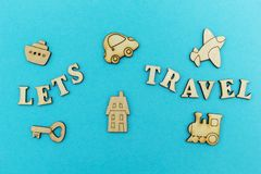 Wooden figures of an airplane, a train, a ship, a car. The inscription `let`s travel` on a blue background. royalty free stock photos