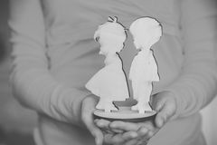 Wooden figures boy and girl in the hands of women Stock Photos