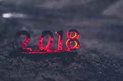 Wooden figures 2018 are burned in a flame. Conceptual photo end of the year. Wooden figures 2018 are burned in flame. Conceptual photo end of the year stock image