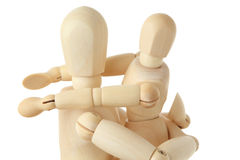 Wooden figures of child embracing parent Royalty Free Stock Photo