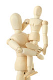 Wooden figures of child sitting on hands of parent stock photos
