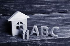 Wooden figures of children stand in a row from small to large near the letters of the English alphabet abc. stock image