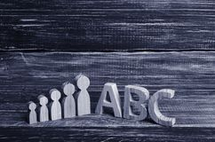 Wooden figures of children stand in a row from small to large stock images