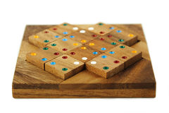 Wooden figures with color dots assemble in puzzle Royalty Free Stock Photography