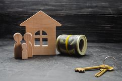 The wooden figures of the family stand near a wooden house, keys and money. Buying and selling a house. Good life, moving to new a royalty free stock photos