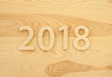 Wooden figures forming 2018, carved from light wood on the backg Stock Photo