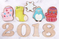 Wooden figures 2018 and gingerbreads. Sweet mittens, a boot, a penguin and a snowflake. Children`s New Year`s composition stock images