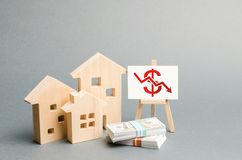 Wooden figures of houses and a poster with a symbol of falling value. concept of real estate value decrease. low liquidity. And attractiveness of assets royalty free stock images