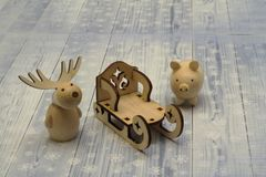 Wooden figures. New Year. Deer, pig and graceful sleigh on light background. Handmade royalty free stock images