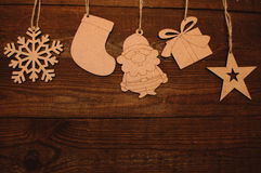 Wooden figures. New Year natural wooden figures hanging on a wooden boards background Stock Image
