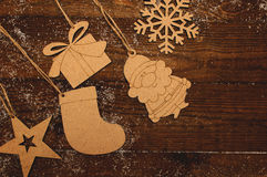 Wooden figures. New Year natural wooden figures hanging on a wooden boards background Stock Photography