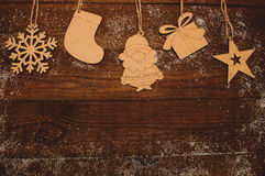 Wooden figures. New Year natural wooden figures hanging on a wooden boards background Stock Images