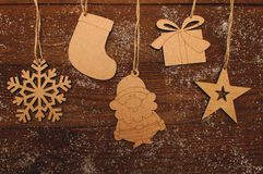 Wooden figures. New Year natural wooden figures hanging on a wooden boards background Royalty Free Stock Images