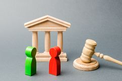 Wooden Figures Of People Standing Near The Judge`s Gavel. Litigation. Business Rivals. Conflict Of Interest. Law And Justice. The Royalty Free Stock Photography