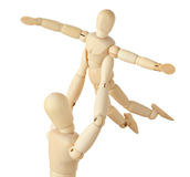 Wooden figures of parent carring child over head Stock Photography