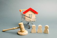Wooden figures of people, a house in a supermarket trolley and a judge`s hammer. Auction. Public sale of real estate. Clarification of ownership of property royalty free stock photography