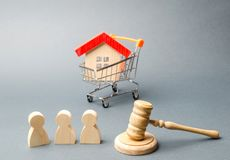 Wooden figures of people, a house in a supermarket trolley and a judge`s hammer. Auction. Public sale of real estate. Clarification of ownership of property royalty free stock photo