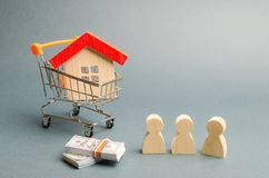 Wooden figures of people, a house in a supermarket trolley and a judge`s hammer. Auction. Public sale of real estate. Clarification of ownership of property stock images