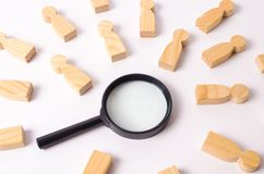 Wooden figures of people lie around a magnifying glass on a white background. Hiring for work, tracing people. The concept of the search for people and workers stock images