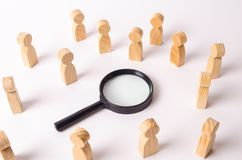 Wooden figures of people stand around the magnifying glass and look to the center. The concept of the search for people and worker. S, human resources. Hiring royalty free stock image