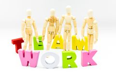 Wooden figures posing as business men between the words TEAM and WORK. Isolated on white. Team, unity and collaboration concept stock images