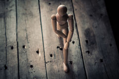 Wooden figurine balancing on an old wooden table. Stock Image